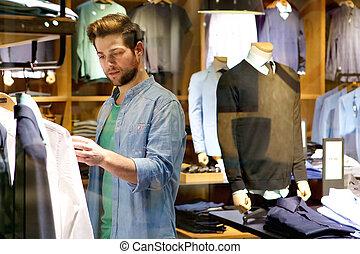 Junger Mann, der Kleider ansieht, die er im Laden kaufen kann.