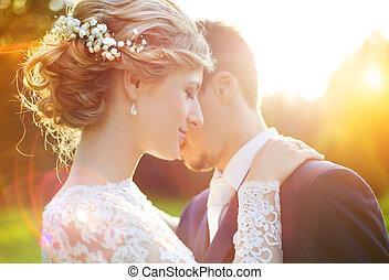 Junges Hochzeitspaar auf Sommerwiese.