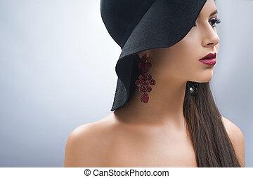 Junges Mädchen mit schwarzem Hut.