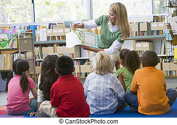 Kindergarten-Lehrer lesen zu Kindern in der Bibliothek.