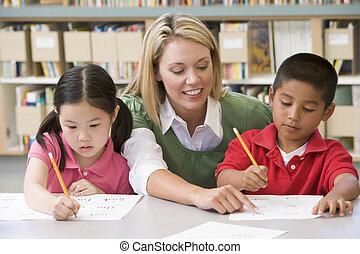 Kindergartenlehrer, der Schüler beim Schreiben hilft