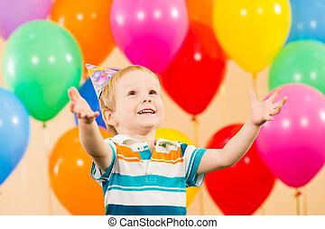 Lächelnder Junge mit Ballons auf der Geburtstagsparty