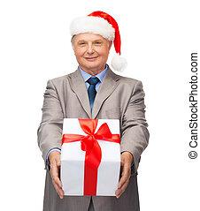 Lächelnder Mann im Anzug und Santa Helper Hut mit Geschenk