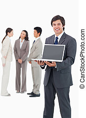 Lächelnder Verkäufer zeigt Laptop-Screening mit Team hinter ihm
