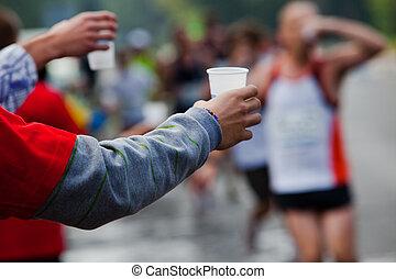 Läufer nehmen ein Wasser in einem Marathonrennen