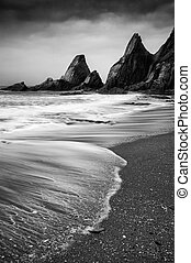 Landscape seascape of jagged and rugged rocks on coast with.