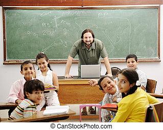 Lehrer im Klassenzimmer mit seinen kleinen glücklichen Schülern.
