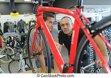 Männer, die über Fahrradaufführungen im Fahrradladen reden.