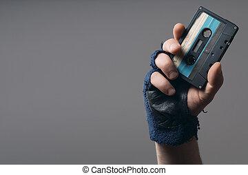 Männliche Hand mit Handschuh mit altem Musikband.
