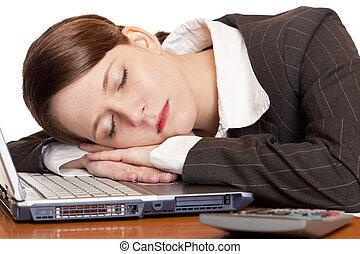 Müde überarbeitete Geschäftsfrau schläft auf Laptop im Büro
