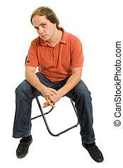 Mann auf einem Stuhl.
