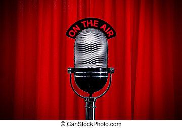 Mikrofon auf der Bühne mit Scheinwerfer auf dem roten Vorhang