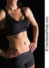 Mitten in der schlanken, fitten Frau, die in Sportkleidung posiert