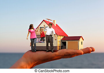 Modell des Hauses mit Garage auf der Hand gegen Meer und Familie mit Mädchen Collage.