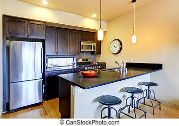 Moderne braune Küche mit Bar und Hockern.