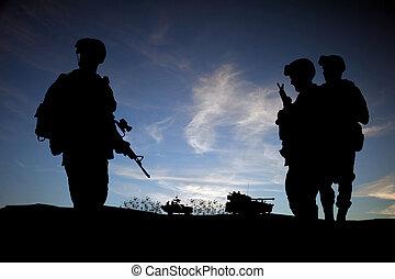 Moderne Tagessoldaten im Nahen Osten, Silhouette vor Sonnenuntergang mit Fahrzeugen im Hintergrund