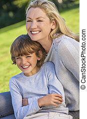 Mutter Sohn-Frau-Junge, das Kind sitzt draußen in der Sonne.