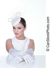Mysteriöse Frau mit eleganten weißen Hüten und Glühen.
