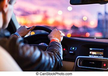 Nachts Auto fahren - nachts fährt ein Mann sein modernes Auto