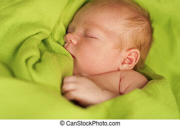 Neugeborene schlafen auf einer grünen Decke