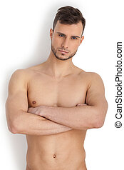 Portrait der Männlichkeit. Einfühlsamer junger muskulöser Mann, der auf die Kamera schaut und die Arme kreuzt, während er auf weißem Hintergrund isoliert steht