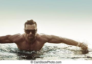 Portrait eines ernsthaften Mannes in einem tropischen Pool.