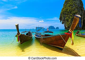 Reiselandschaft, Strand mit blauem Wasser und Himmel im Sommer. Thailand ist eine wunderschöne Insel und traditionelles Holzboot. Ein tropisches Paradies.