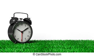 Retro schwarzer Wecker auf Gras, isoliert auf weißem Hintergrund.