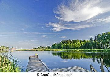 Ruhiger See unter lebendigem Himmel im Sommer