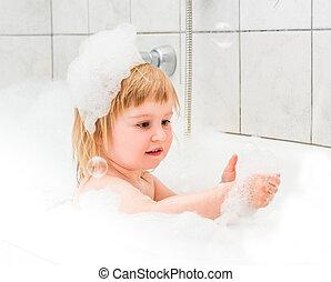 Süß zwei Jahre alte Babybäder in einem Bad mit Schaum.