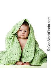 Süßes Baby, das zwischen der grünen Decke sitzt.