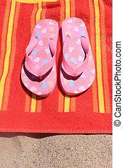 Sandalen am Strandhandtuch