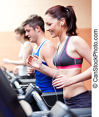 Schöne Athletin, die auf einer Maschine steht und die Musik in einem Fitnesscenter hört
