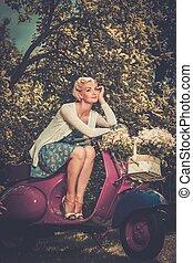 Schöne blonde Frau, die auf einem Retroroller sitzt.