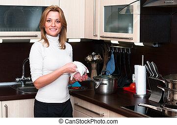 Schöne, glückliche, lächelnde Frau im Kücheninneren. Nur eine Person