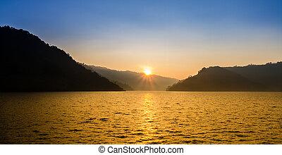 Schöne Sonnenaufgänge über Berg und See.