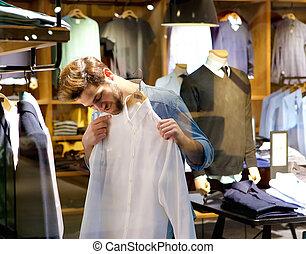Schöner junger Mann, der Kleider kauft.