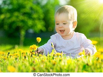 Schönes, glückliches kleines Mädchen, das auf einer grünen Wiese sitzt, mit gelben Blumendelions auf der Natur im Park
