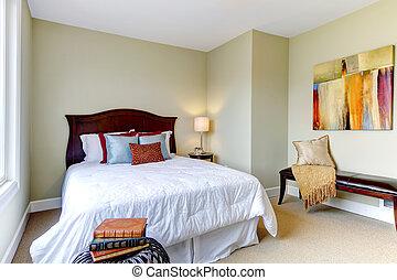 Schlafzimmer mit weißem Bett, grüne Wände und schönem Dekor.