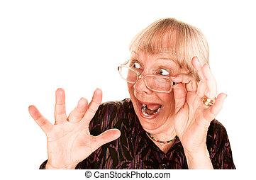 Schockierte ältere Frau, die über ihre Brille schaut