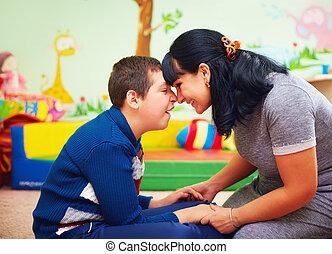 Schrecklicher Moment. Portrait von Mutter und ihrem geliebten Sohn mit Behinderung in Rehabilitationszentrum