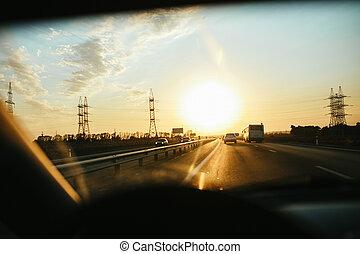 Selektive Fokussierung Asphaltstraße durch Windgläser, Auto fahren bei Sonnenuntergang. Reisehintergrund