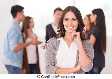 Sie ist ein Teamführer. Selbstbewusste junge Frau, die Hand auf Kinn und Lächeln hält, während Gruppe von Menschen im Hintergrund kommunizieren