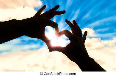 Silhouette Hände in Herzform und blauem Himmel.