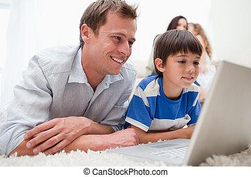 Sohn und Vater benutzen Laptop auf dem Teppich