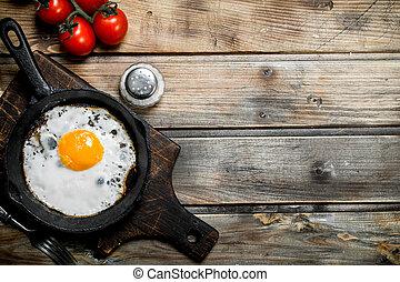 Spiegelei in einer Pfanne mit Tomaten.