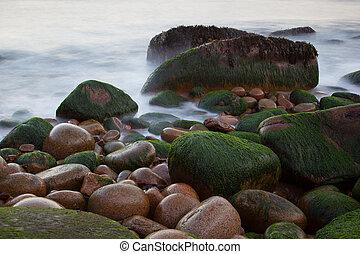 Steine auf otter Klippen Küste mit verschwommenem Wasser, Acadia Nationalpark, Maine, USA.