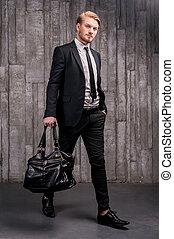 Stylish, hübsch. Volle Länge von gutaussehenden jungen Mann mit einer schwarzen Tasche