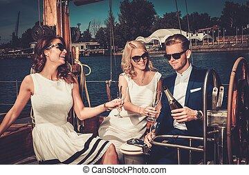 Stylish reiche Freunde haben Spaß auf einer Luxus-Yacht.