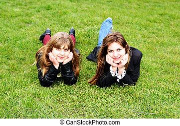 Teen Girls liegen auf dem grünen Gras